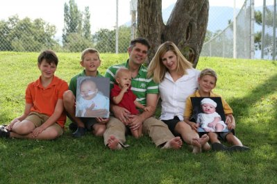 Family, sitting under tree, holding photos, facial defects